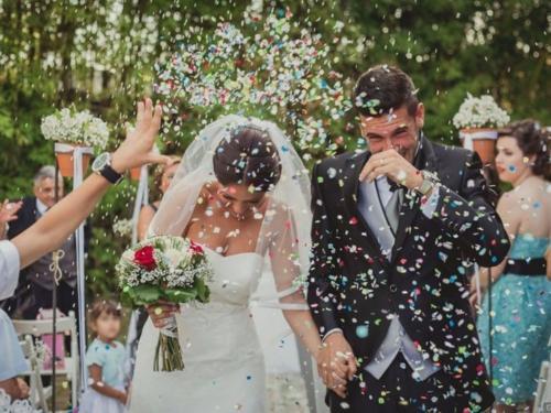 Novios recien casados, invitados tiran confeti.